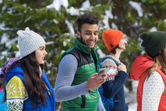 Hispanic Man Using Smart Phone Chatting Online Snow Forest Young People Group Walking Outdoor Winter. Pine Woods stock photography