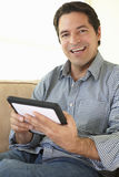 Hispanic Man Using tablet computer At Home Stock Images