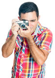 Hispanic man using a vintage looking compact camera Royalty Free Stock Image