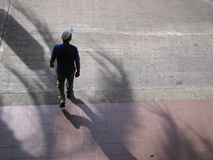 Hispanic man walks on a street and looking to the side, aerial view.  Royalty Free Stock Image