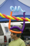 A Hispanic man wares multi-colored balloons Royalty Free Stock Image