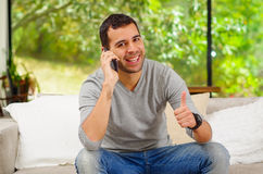Hispanic man wearing denim jeans with grey sweater. Sitting in sofa talking on phone and giving thumbs up to camera smiling Stock Photo