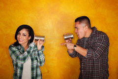 Hispanic Man and Woman Communicating. Attractive Hispanic man and woman communicate through tin cans Royalty Free Stock Photography