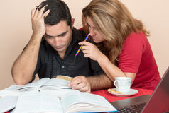 Hispanic man and woman studying at home Stock Images