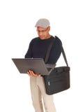 A Hispanic man working on his laptop. Stock Image