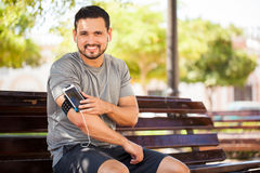 Hispanic man working out with music. Portrait of a handsome young Hispanic man exercising outdoors in a park and listening to music with a smartphone and armband Stock Photos