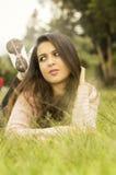 Hispanic model brunette lying on grass facing Royalty Free Stock Photo