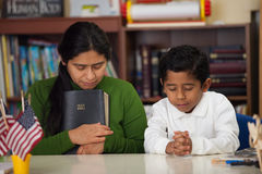 Hispanic Mom and Boy Praying in Home-school Setting During Worship Royalty Free Stock Photos