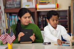 Hispanic Mom and Boy in Home-school Setting During Worship. Hispanic Mom and Boy in Home-school Environment During Worship royalty free stock image