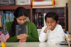 Hispanic Mom and Boy Praying During Worship. Hispanic Mom and Boy in Homeschool Environment During Worship royalty free stock images