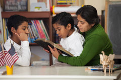 Hispanic Mom and Boys Reading the Bible During Worship. Hispanic Mom and Boys During Worship royalty free stock photo