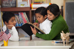 Hispanic Mom and Boys Reading the Bible During Worship Royalty Free Stock Photos