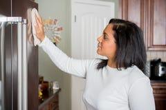 Hispanic Mom Cleaning. Happy hispanic mom cleaning her new refrigerator royalty free stock image
