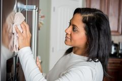 Hispanic Mom Cleaning. Happy hispanic mom cleaning her new refrigerator royalty free stock photography