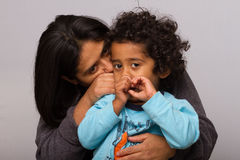 Hispanic Mom with Curly Hair Child. On Gray Background royalty free stock images