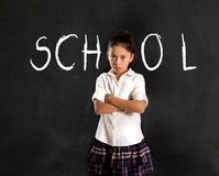 Hispanic moody little girl in uniform standing upset in front of blackboard Royalty Free Stock Photos