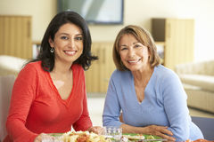Hispanic Mother With Adult Daughter Enjoying Meal At Home Stock Photo