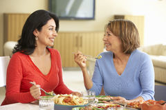Hispanic Mother With Adult Daughter Enjoying Meal At Home Royalty Free Stock Image