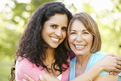 Hispanic Mother And Adult Daughter Relaxing In Park Stock Image