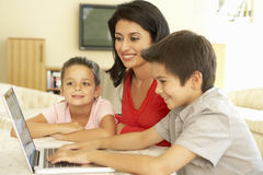 Hispanic Mother And Children Using Computer At Home Royalty Free Stock Images