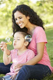 Hispanic Mother And Daughter Blowing BubblesIn Park Stock Photography