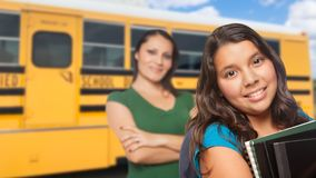 Hispanic Mother and Daughter Near School Bus. Proud Hispanic Mother and Daughter Next to a School Bus royalty free stock photos