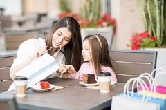 Mother and daughter looking at stuff they bought in a cafe Royalty Free Stock Photo