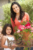 Hispanic Mother And Daughter Working In Garden Tidying Pots Royalty Free Stock Images