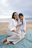 Hispanic mother and girl sitting on beach blanket Stock Photo