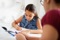 Hispanic Mother Helping Girl Doing School Homework At Home. Happy caucasian family at home. Hispanic mother and female child. Latina mom helping daughter with Royalty Free Stock Images