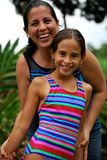 Hispanic Mother and  her beautiful  daughter. Beautiful Hispanic mother and daughter together.  The mother is behind the daughter.  Both are smiling Stock Image