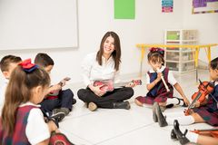 Hispanic music teacher in a preschool classroom. Portrait of an attractive Hispanic brunette teaching music to a group of preschool pupils stock images