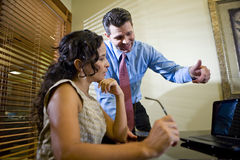 Hispanic office worker working with male colleague Royalty Free Stock Photo