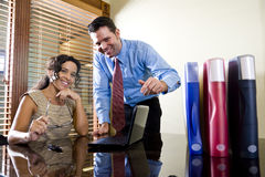 Hispanic office worker working with male colleague Royalty Free Stock Photography