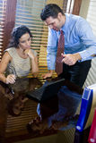 Hispanic office worker working with male colleague Royalty Free Stock Images