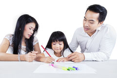 Hispanic parents help their daughter studying Stock Photography