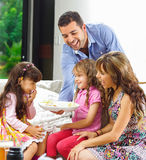 Hispanic parents with two daughters eating from a Stock Photo