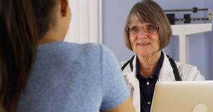 Hispanic patient talking to Senior doctor in office Royalty Free Stock Photo