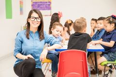Hispanic preschool teacher loving her job. Portrait of a gorgeous Hispanic preschool teacher loving her job and having fun with her pupils royalty free stock photo