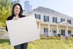 Hispanic Realtor Holding Blank Sign In Front of House. Smiling Hispanic Female Holding Blank Sign In Front of Beautiful House Royalty Free Stock Photos