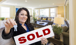 Hispanic Realtor with Keys and Sold Sign in Living Room. Happy Hispanic Woman with House Keys and Sold Sign in Beautiful Living Room Stock Photos