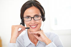 Hispanic receptionist conversing on her headphones Stock Photos