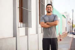 Hispanic runner doing some exercise outdoors. Portrait of a handsome young Hispanic man in sporty outfit standing in a street ready to exercise and go jogging Stock Photo