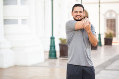 Hispanic runner stretching his arms. Portrait of a happy Hispanic young runner stretching his arms before working out in the city Stock Images