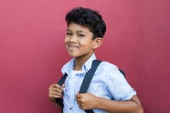 Hispanic school boy. Young hispanic school boy ready with backpack to go to elementary school. Portrait of happy middle eastern schoolboy standing against red stock images