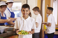 Hispanic schoolboy holds a plate of food in school cafeteria stock photos
