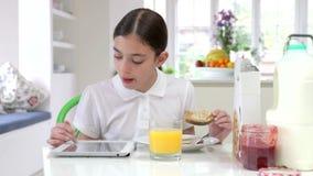 Hispanic Schoolgirl With Digital Tablet Eating Breakfast stock video