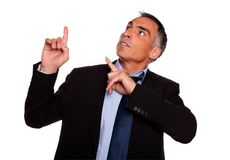 Hispanic senior businessman pointing up Stock Photography
