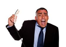 Hispanic senior businessman screaming with a phone. Portrait of a very stressed senior businessman screaming with a phone against white background Royalty Free Stock Photography