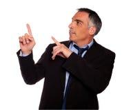 Hispanic senior entrepreneur pointing up Stock Photos